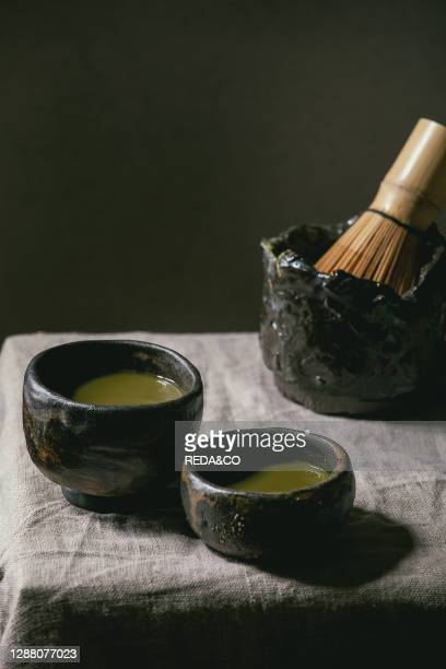 Japanese matcha green tea in two wabi sabi cups. Bamboo whisk on grey linen table cloth.