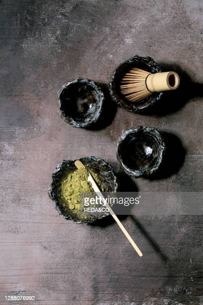 Japanese matcha green tea powder in craft ceramic bowl. Couple of cups. Bamboo whisk over dark texture background. Flat lay. Space.