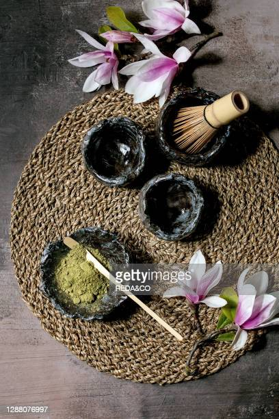 Japanese matcha green tea powder in craft ceramic bowl. Couple of cups. Bamboo whisk and pink magnolia flowers on straw napkin over dark texture...