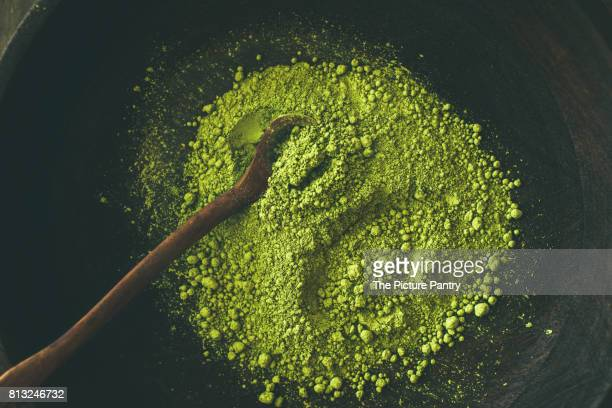 Japanese Matcha green tea powder in dark wooden bowl with spoon, top view