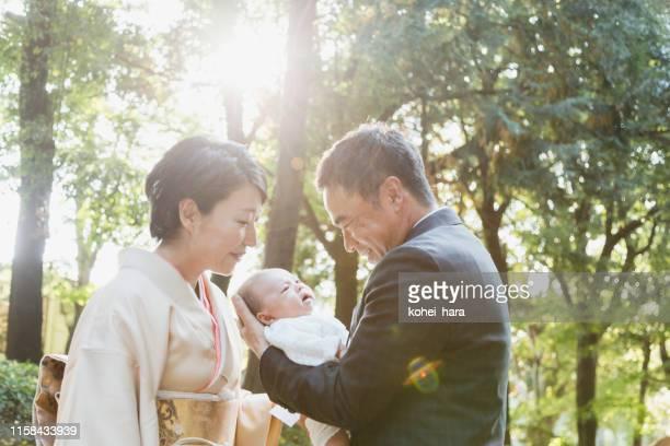 日本の成熟したカップルは、彼らの新生児を運ぶフォーマルな服を着て - 着物 ストックフォトと画像