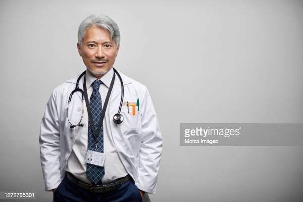 japanese mature doctor in lab coat against white background - doctor stock pictures, royalty-free photos & images