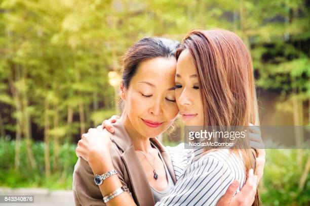 Japanese mature mother outdoors embracing adult daughter in peaceful reunion eyes closed