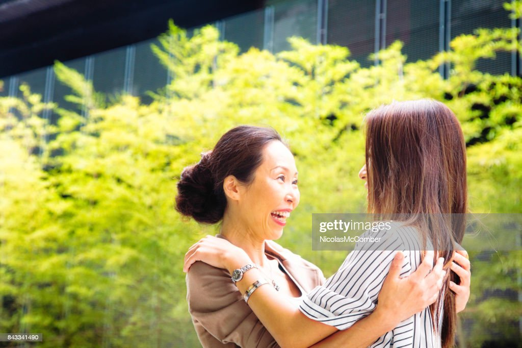 Japanese mature mother welcomes her daughter and smiles at her cheerfully :  Stock Photo