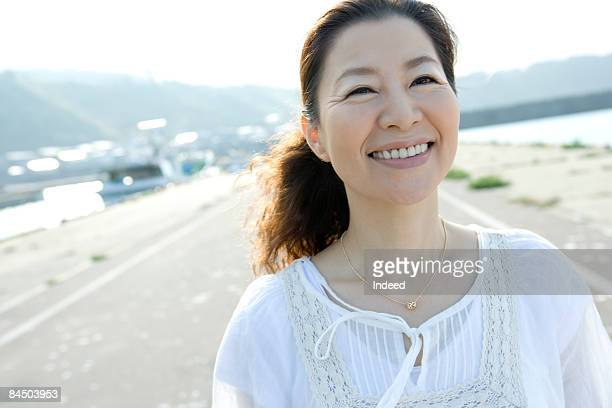 Japanese mature woman smiling on port