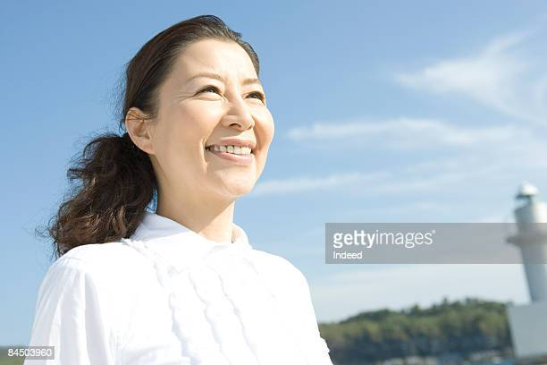 Japanese mature woman smiling on port, portrait
