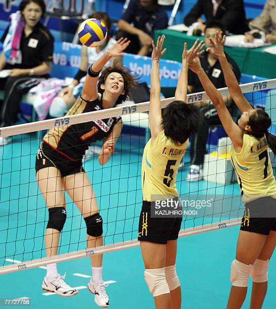 Japanese Megumi Kurihara spikes the ball past Thailand's blockers, Pleumjit Thinkaow and Narumon Khanan during their second round match of the...