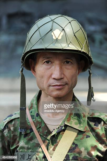 Japanese men clad in outdated military costumes march in to pay respects to the country's war dead at the Yasukuni Shrine in Tokyo on August 15 2015...