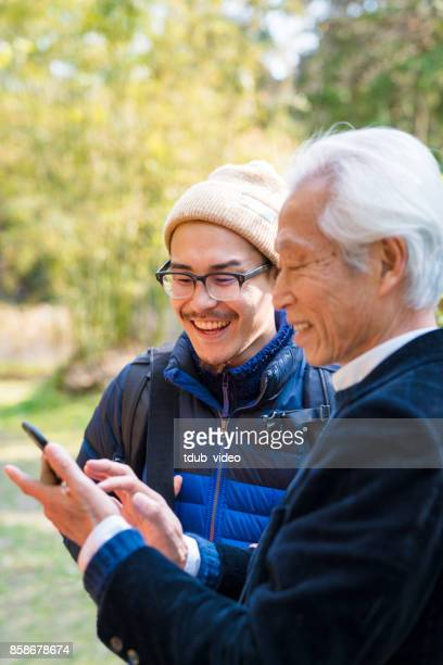 Japanese men laughing looking at phone