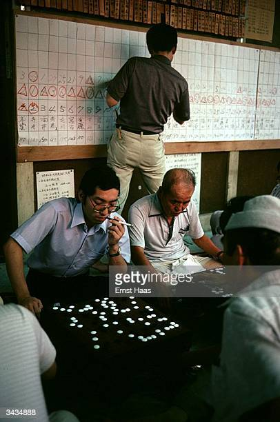 Japanese men playing 'Go' behind them a scoreboard is being filled in