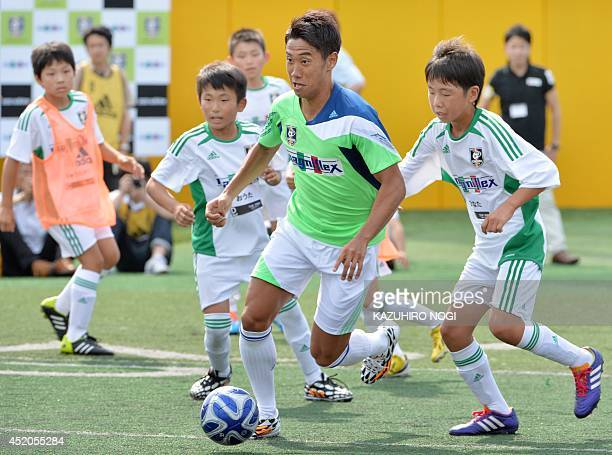 Japanese midfielder Shinji Kagawa of English Premier League side Manchester United displays his skills during a football clinic with children at...