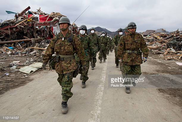 Japanese military march during a search and rescue mission scouring the rubble of a village destroyed by the devastating earthquake and tsunami on...