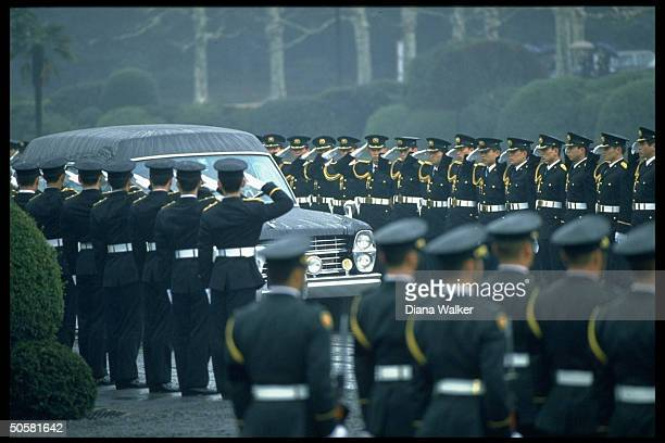 Japanese military personnel saluting late Emperor Hirohito's hearse as it passes in burial garden