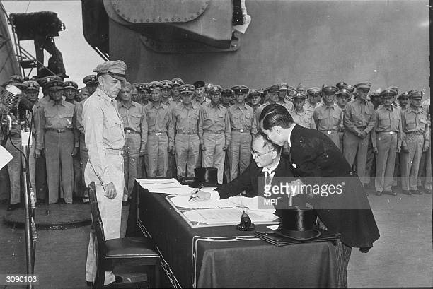 Japanese Minister of Foreign Affairs Mamoru Shigemitsu, signs the Japanese Instrument of Surrender aboard the USS Missouri in Tokyo Bay at the end of...