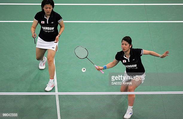 Japanese Mizuki Fujii plays a shot as her partner Reika Kakiiwa watches in their match against Denmark's Lena Frier Kristiansen and Marie Ropke...