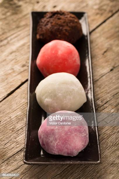 japanese mochis on wooden table - mochi stock photos and pictures