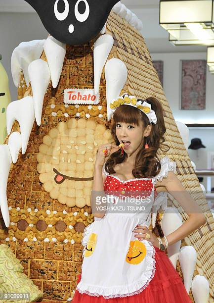 Japanese model Aki Hoshino displays a piece of cookie before the 21m tall sweet house decorated with cookies and sugar candies for the sales...