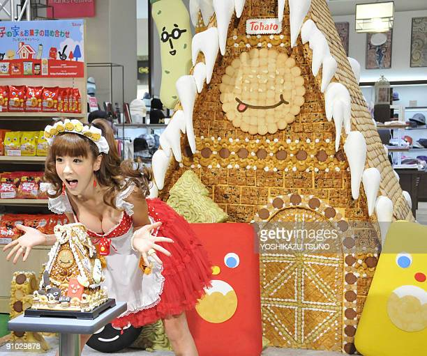 Japanese model Aki Hoshino displays a small replica and the 21m tall sweet house decorated with cookies and sugar candies for the sales promotion by...