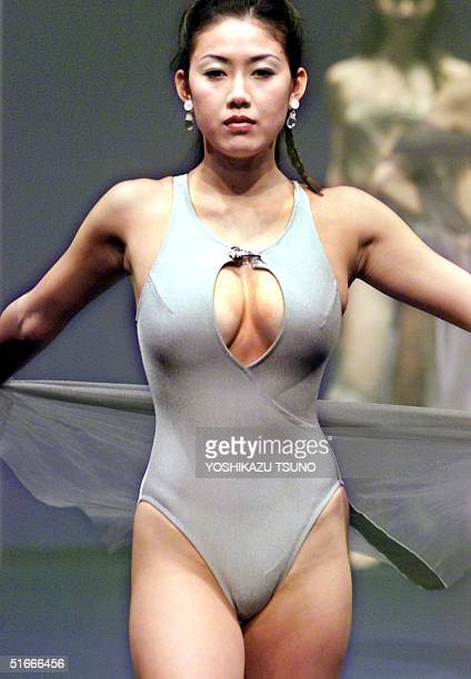 Japanese model shows off a swimsuit with transparent robes during Japanese apparel giant Teijin's '99 swimwear collection in Tokyo 06 January AFP...