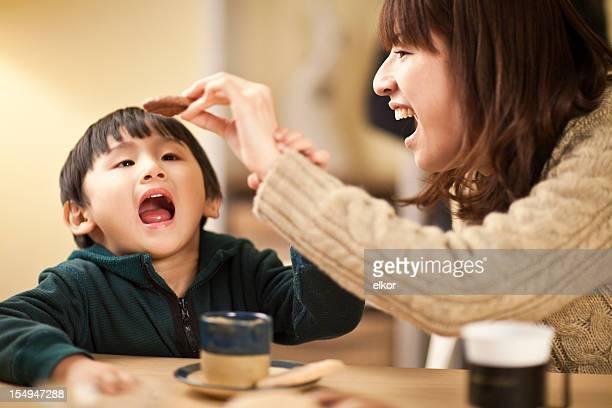 Japonês mãe e filho brincando com Biscoitos na mesa