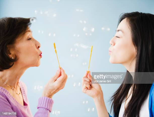 Japanese mother and daughter blowing bubbles