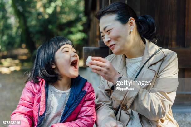 日本人の母と娘一緒におにぎりを食べて
