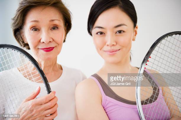 Japanese mother and daughter holding tennis racquet