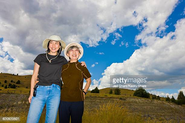 Japanese mother and daughter standing on hillside
