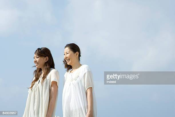 Japanese mother and daughter standing, smiling