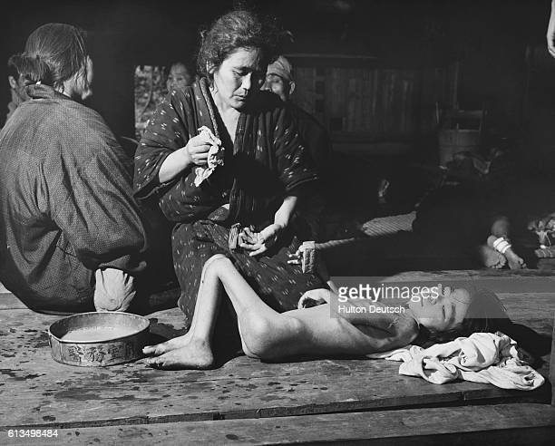 A Japanese mother bathes her starving child 1945