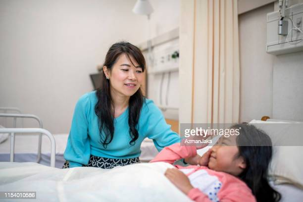 japanese mother comforting young daughter in the hospital - next to stock pictures, royalty-free photos & images