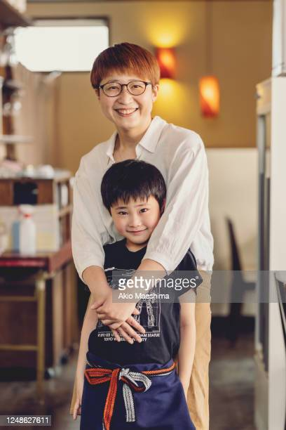 a japanese mother holing his son at iazakaya, japanese pub - single mother stock pictures, royalty-free photos & images