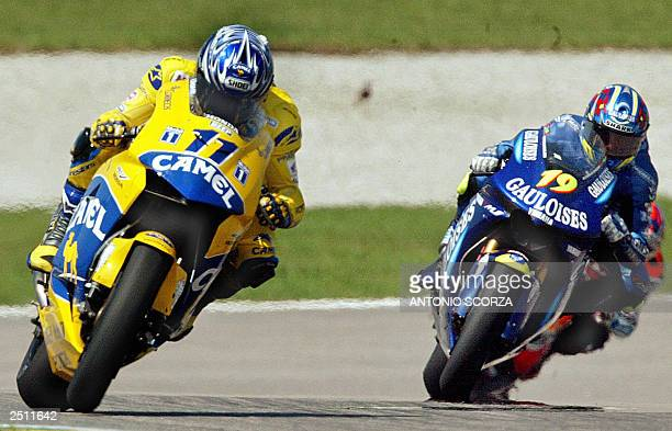 Japanese MotoGP rider Tohru Ukawa powers his Honda Pons followed by the French Olivier Jacques on Yamaha 19 September 2003 during the second training...