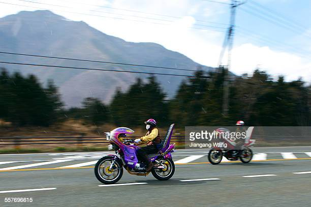 Japanese motorcycle gangsters running on the road when it is sunny and snowing