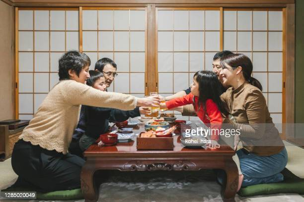 japanese mulit generation family drinking a toast before eating osechi ryori, japanese new year dishes, on the dining table in japanese room - osechi ryori stock pictures, royalty-free photos & images
