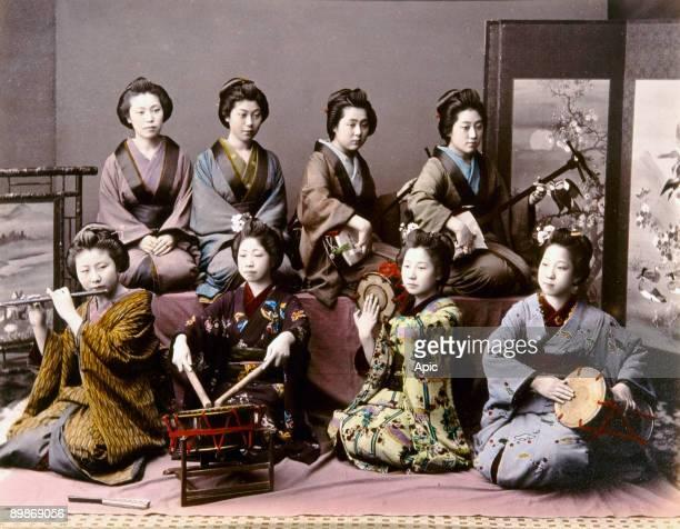 Japanese musicians JAPAN MUSICIANS c1890 Playing the shamisen tsudzumi Fuye and taiko Handtinted albumen photograph by Kimbei c1890