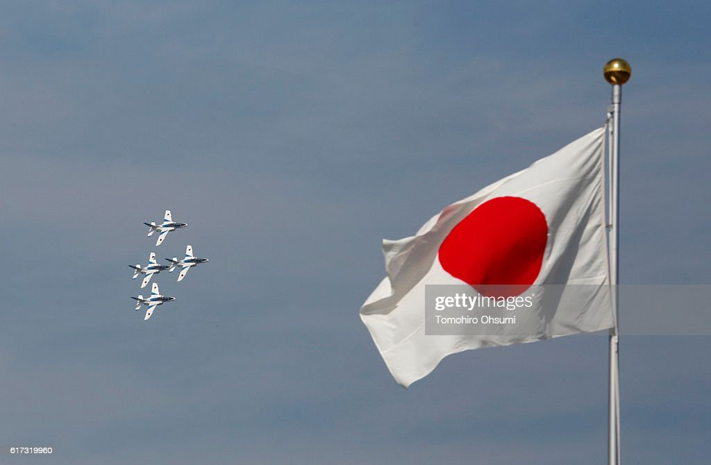 A Japanese national flag flies as aircrafts from Japan's Air Self-Defense Force's acrobatic flight team, known as Blue Impulse, fly during the annual review at the Japan Ground Self-Defense Force Camp Asaka on October 23, 2016 in Asaka, Japan.