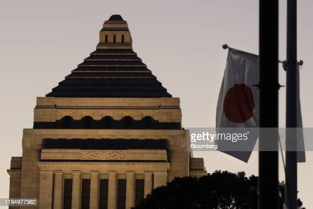 Japanese national flag flies in front of the National Diet building at dusk in Tokyo, Japan, on Monday, Jan. 20, 2020. Prime Minister Shinzo Abe...