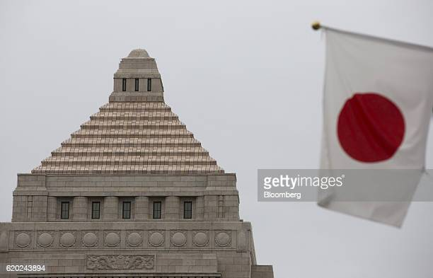 """Japanese national flag flies in front of the National Diet building in Tokyo, Japan, on Wednesday, Nov. 2, 2016. The Bank of Japan will """"make policy..."""
