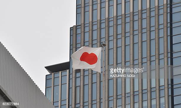 Japanese national flag flies on the roof of a building in Tokyo on November 14 2016 Official data showed on November 14 that Japan's economy grew a...