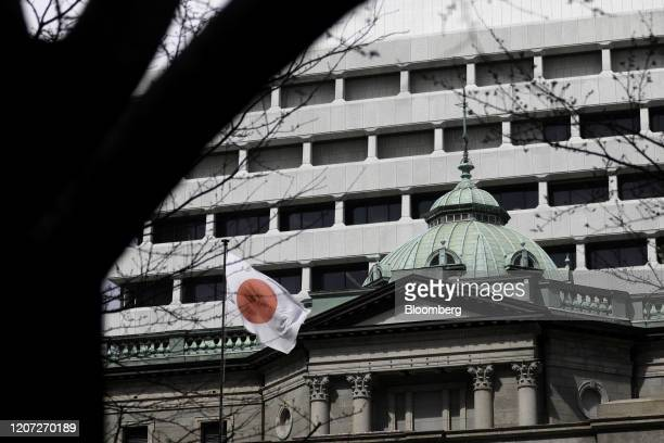 Japanese national flag flies outside the Bank of Japan headquarters in Tokyo, Japan, on Monday, March 16, 2020. The Bank of Japan strengthened...