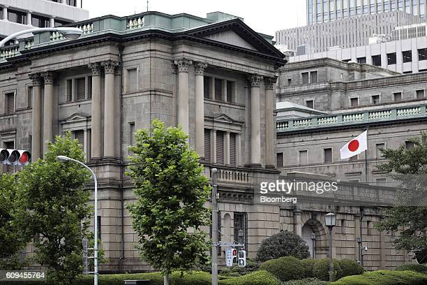 Japanese national flag flies outside the Bank of Japan headquarters in Tokyo, Japan, on Wednesday, Sept. 21, 2016. The BOJ shifted the focus of its...