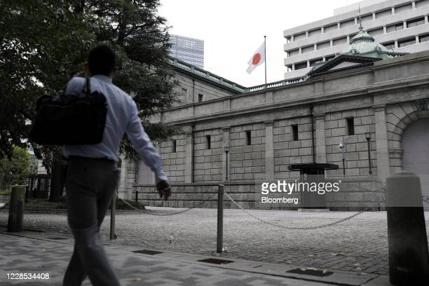 Japanese national flag flies while a pedestrian walks past the Bank of Japan headquarters in Tokyo, Japan, on Monday, Sept. 14, 2020. The Bank of...