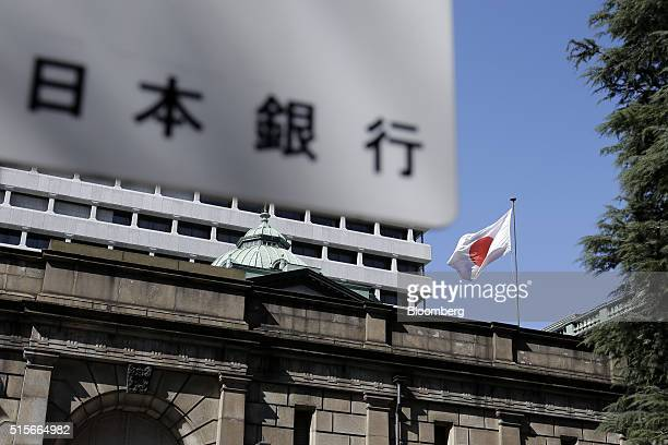 A Japanese national flag flies while signage for the Bank of Japan is displayed outside the central bank's headquarters in Tokyo Japan on Tuesday...