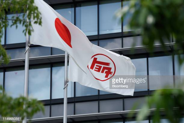 Japanese national flag, left, and Toyota Motor Corp. Flag featuring the old logo fly at the company's headquarters in Toyota City, Aichi Prefecture,...