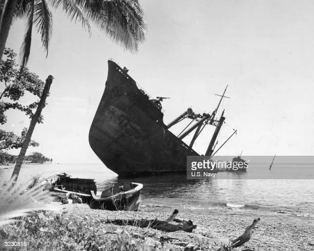 Japanese naval vessel lies half-submerged offshore, sunk by the U.S. Navy in the battles at Guadalcanal, Solomon Islands. A small boat sits on the...