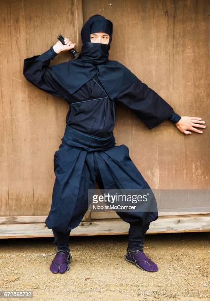 Japanese ninja in black costume hiding against a wall in ready position