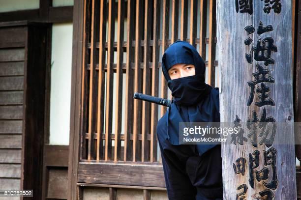 Japanese ninja in black costume hiding in Edo village behind wooden sign