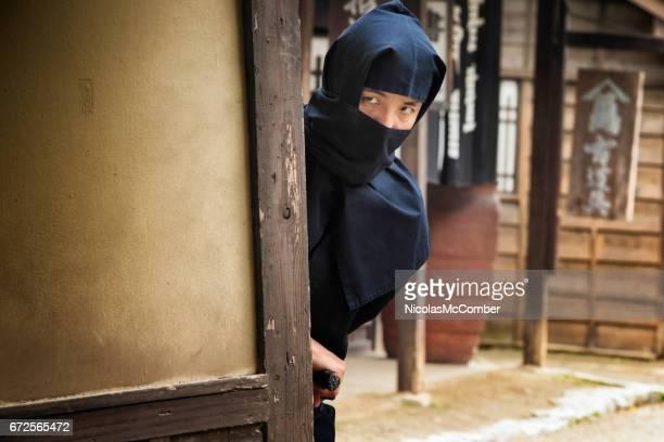 Japanese ninja in black costume hiding in Edo village