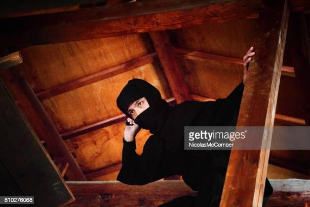 木製の屋根裏部屋を攻撃する準備ができてを隠す黒い衣装で日本の忍者